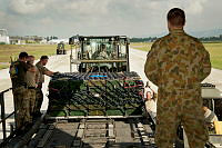 Australian military personnel watch as an airload team from the Danish and United States Defence Forces loads a Royal Australian Air Force C-17A Globemaster aircraft with 50 tonnes of military stores at Tirana Airport, Albania, prior to its delivery to northern Iraq.