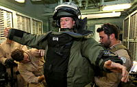 Dene Hills of the Australian cricket team is assisted by Able Seaman Clearance Divers Matthew Brooke (left) and Jackson Sharp (right), into a MED ENG EOD-9 Bomb Suit, while touring HMAS Toowoomba.