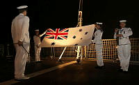 HMAS Toowoomba conducts a ceremonial sunset on the flight deck, in honour of the Australian cricket team.