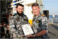 Commanding Officer HMAS Success, Captain Justin Jones, RAN (right) presents Leading Seaman Marine Technician Gregory Williams with his Marine Systems Manager Certificate in a small ceremony on the Flight Deck on HMAS Success during Operation MANITOU.