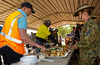 Prime Minister of Australia, The Hon Tony Abbott MP, enjoys some freshly-baked scones as Australian Army soldier Private Justine Burrows looks on during Australian Defence Force (ADF) support to the Prime Minister's visit to North East Arnhem Land in September 2014.