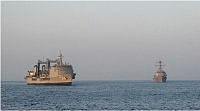 United States Ship Dewey (right) lends support to HMAS Success while conducting a boarding in the Middle East Region.