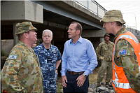 Prime Minister of Australia, the Honourable Tony Abbott, MP (centre) talks with the Commanding Officer 3rd Brigade Brigadier Roger Noble, DSC, CSC during a visit to a local work site in the wake of Cyclone Marcia.