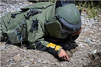 An Afghan National Defense and Security Forces student in an Explosive Ordnance Disposal (EOD) suit checks the ground for detonation cable during an explosive ordnance test at the EOD School at the Central Training Centre in Kabul, Afghanistan.