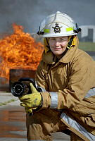 Leading Aircraftwoman (LACW) Melanie Schenk prepares the fire hose to extinguish a simulated fire emergency. LACW Schenk is the only female Firefighter within No. 381 Expeditionary Combat Support Squadron.