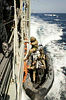 A Royal Marine from HMS Somerset disembarks HMAS Darwin on completion of a cross deck of personnel between the two ships.