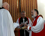 Right Reverend Ian Keese Lambert receives a Bible from Archdeacon Eric Burton as he is commissioned as the Anglican Bishop to the Australian Defence Force.