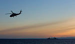 Royal Australian Navy Seahawk Helicopter 'Tiger 80', currently embarked on HMAS Perth, flies past the Spanish combat support ship ESPS Cantabria after launching to conduct night flying operations as part of Exercise Talisman Saber 2013.