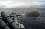 HMAS Perth fires her 5-inch gun during air defence exercises with US Navy fleet units.