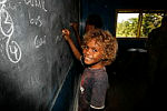 Morris, a student from Gifu Primary School, is proud as punch as he shows how he can write his name on the board.