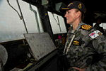 The Commanding Officer of HMAS Success Captain Allison Norris RAN scans the ocean from the ship's bridge during the search for the missing Malaysia Airliner MH370.