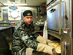 ABML-C Stephen Finnigan checks on a tray of pastry in the galley of MV Seahorse Standard