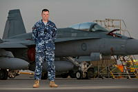 Royal Australian Air Force Armament Officer Flying Officer Cameron Sheridan stands before an F/A-18A Hornet aircraft during his Operation OKRA deployment at the main air operating base in the Middle East Region.