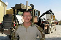 Corporal Glenn Maag with his truck during the redeployment and disposal of equipment at Camp Baker, Kandahar Airfield, Afghanistan.