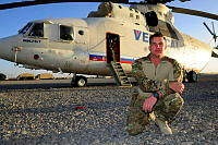 "Corporal Drew Charlwood an Army Cargo Specialist Supervisor or ""Termite,"" kneels in front of the Russian Mi-26 heavy transport helicopter known as Blinkey."