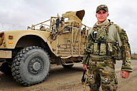 Leading Aircraftman Greg Polak stands at the front of a Mine Resistant Ambush Protected Vehicle (MRAP).