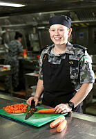 Seaman Maritime Logistics Chef Peta Large dices carrots preparing for dinner on HMAS Choules during Exercise Sea Dawn 2014.