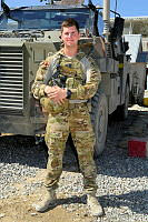 Trooper Samuel Perkins stands before a Bushmaster Protected Mobility Vehicle (PMV) while deployed with the 205th Corps Coalition Advisory Team (205 CAT) Force Protection Platoon.