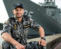 Seaman Combat Systems Operator Sam Greenland at Fleet Base East with HMAS Melbourne in the background at Garden Island Naval Base in Sydney.