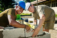 Australian soldier Sapper Brad Schopp (right) from 21st Construction Squadron, 6 Engineer Support Regiment in Brisbane, and Timor Leste Defence Force Engineer Sebastiao da Silva conduct brickwork at Comoro Intermediate School in Dili, East Timor, during Exercise Pacific Partnership 2014.