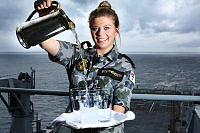 Able Seaman Maritime Logistics Steward Angela Stephenson pours some refreshments onboard HMAS Choules