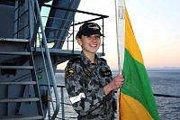 Seaman Communication and Information Systems sailor Annaleise Easlea raises the pennant flag during a sunset ceremony onboard HMAS Choules, in Jervis Bay.