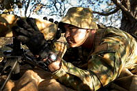 Australian Army Private Conrad Bruppacher scans his arcs for potential enemy activity from his overwatch position during Exercise Northern Shield 2015.