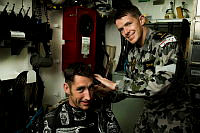Royal Australian Navy sailor Able Seaman (AB) Marine Logistics - Personnel Jason Duvall (right) cuts hair for Leading Seaman Marine Logistics – Supply Chain Ricky Anderson (left) on HMAS Melbourne, which is patrolling in the Middle East region as part of Operation Manitou.