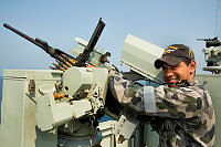 Royal Australian Navy sailor Able Seaman Boatswains Mate Trey Norway maintains a .50cal machinegun aboard HMAS Melbourne, which is patrolling in the Middle East region as part of Operation Manitou.