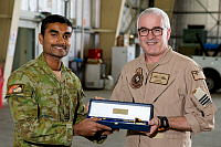 Royal Australian Air Force aircraft technician Aircraftman Lucky Wijesurrya is presented the J.R. Bartram and R.A. Kee sword of honour by the Commanding Officer of the Air Mobility Task Group Wing Commander Charlie Siedentopf at Camp Baird in the Middle East region on March 26.