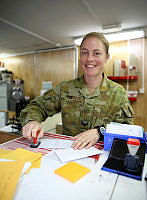 Australian Army soldier Corporal Cassandra Rice processes mail during her work day deployed on Operation Accordion, as an Austrailan Army postal worker at Camp Baird in the Middle East region.