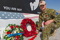 Flight Lieutenant Naomi Holmes lays a string of Poppies on behalf of the Bendigo RSL at Remembrance Day, at Australia's main air operating base in the Middle East Region.