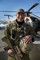 Train Advise Assist Command – Air, Air to Ground Integration Adviser, Flight Lieutenant Thomas Murdock is seen on the flightline at Hamid Karzai International Airport, Kabul, Afghanistan. Behind him is an Afghan Air Force MD-530F Defender helicopter.