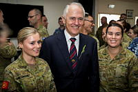 Prime Minister of Australia, the Honourable Malcolm Turnbull poses for a photo with Australian Army Private Sarah Millmore (left) and Private Emma Rose after the Anzac Day 2017 dawn service held at Camp Baird in the Middle East Region.