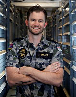 Able Seaman Maritime Logistics - Supply Chain Matthew Bruce stands in the naval stores compartment of HMAS Newcastle while on Operation Manitou in the Middle East Region.