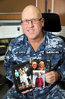 Royal Australian Air Force Flight Lieutenant John Timermanis holding family pictures at Camp Baird on Australia's main operating base in the Middle East region