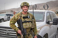 Australian Army Private Mitchell Wheelhouse, currently deployed to Force Protection Element 8, stands in front of an up-armoured sports utility vehicle at Hamid Karzai International Airport in Kabul, Afghanistan.