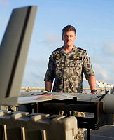 ScanEagle Mission Commander Lieutenant Simon Jeffery with ScanEagle on the flight deck of HMAS Newcastle prior to flying stations in the Middle East region.