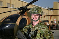 Australian Army Captain Peter Prendergast in front of an Afghan Air Force MD-530F light attack helicopter at Kabul Airport.