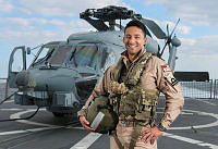 Aviation Warfare Officer Lieutenant Mark Packer stands in front of HMAS Warramunga's embarked MH-60R helicopter during the Ship's deployment to Operation MANITOU.