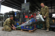 Corporal Malina Rumble (left) and Sergeant Peter Guy work wrap a pallet for transport in preparation for Timor-Leste Aviation Group's return home to Australia.