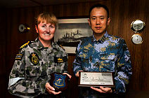 The Commanding Officer of HMAS SUCCESS, Captain Allison Norris, RAN, exchanges ship's plaques with Commander Lin Wan, a Liaison Officer from the People's Liberation Army-Navy destroyer HAIKOU (DDG-171).