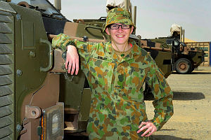 Private Kirsten Steley leans on a Bushmaster Protected Mobility Vehicle at Al Minhad Air Base, United Arab Emirates.