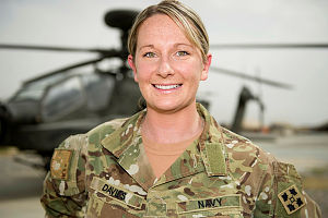Royal Australian Navy pilot, Lieutenant Natalie Davies in front of an AH-64 Apache helicopter at Kandahar Air Field.