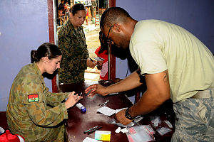 Australian Army preventive medical technician, Private Carly Callaghan (left) sorts medications with United States Air Force pharmacy clerk, Staff Sergeant Jeremy Davis and United States Marine Corps marine at the Cooperative Health Engagement at Tacloban as part of Exercise BALIKATAN.