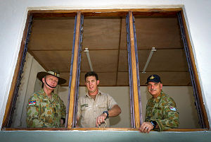 Australian Army officer Colonel Luke Foster, AM, CSC, CSM (left), and Royal Australian Air Force officer Wing Commander Daryll Topp (right), chat with Sapper Col Radunz from 21 Construction Squadron, 6 Engineer Support Regiment as he prepares a window for painting, at the Comoro Health Centre in Dili, East Timor, during Exercise Pacific Partnership 2014.