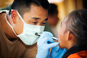 Royal Australian Air Force officer Flight Lieutenant David Liu performs a dental check on a Timorese child at Beto Tasi Primary School in Dili, East Timor, during Exercise Pacific Partnership 2014.