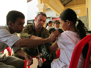 Leading Aircraftman Sean Boller, of No. 2 Expeditionary Health Squadron, conducts a health check on a young girl during a free medical clinic conducted under the auspices of Pacific Partnership 14 at The Hun Sen Primary School in Sihanoukville.