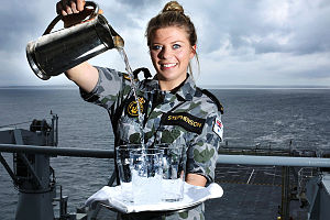 Able Seaman Maritime Logistics Steward Angela Stephenson pours some refreshments onboard HMAS Choules.