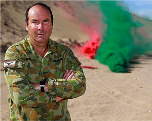 RAAF Warrant Officer John Youd on a weapons range as smoke grenades are disposed of in the Middle East Region.